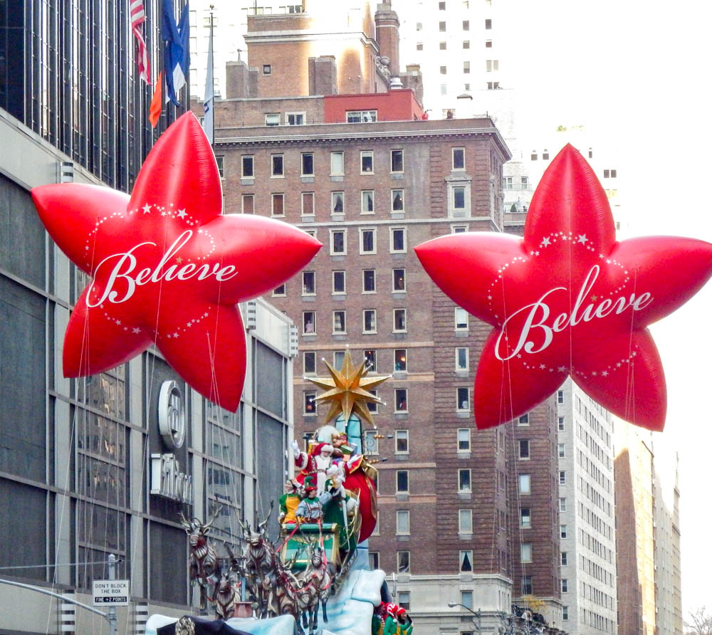 "two red star-shaped parade balloons that say ""believe"" on them at the macys thanksgiving day parade"