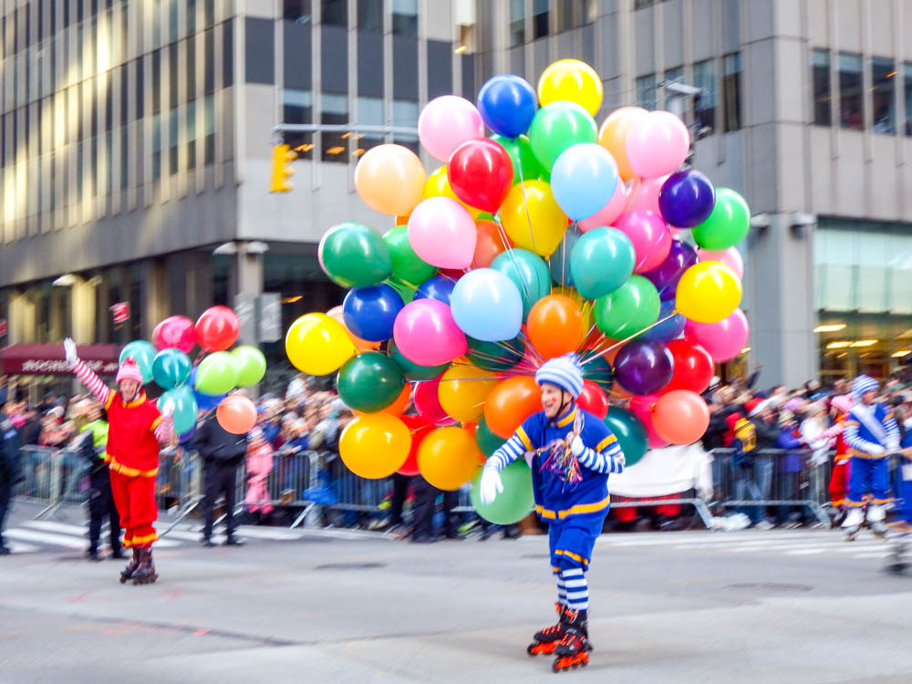 roller-blading clown carrying a hundred balloons