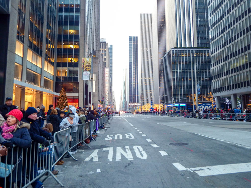 empty street in manhattan lined with lots of people