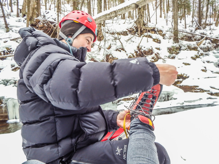 Ice Canyoning in Québec // Why You Should Be All up in This  Our guide putting my crampons on for me - ice canyoning in Québec