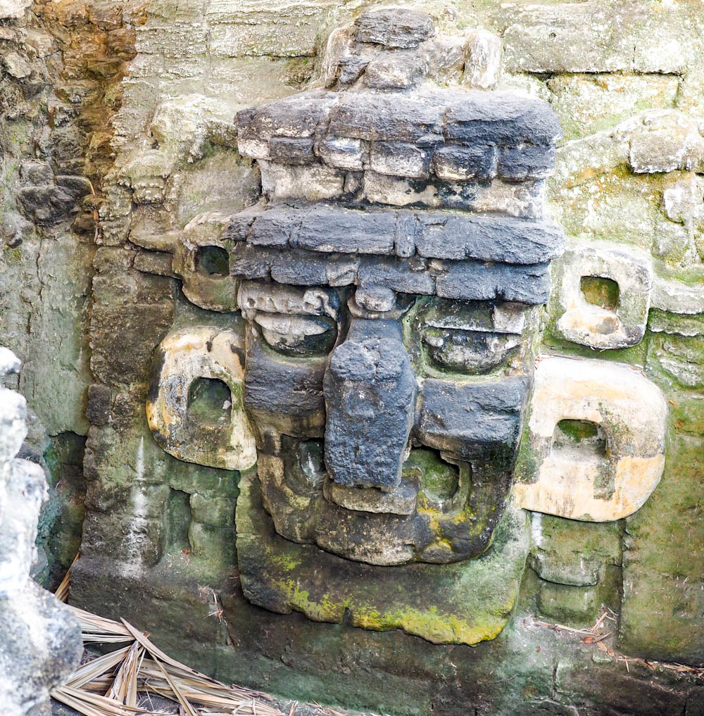 ancient maya face carving in rock on belize to tikal day trip