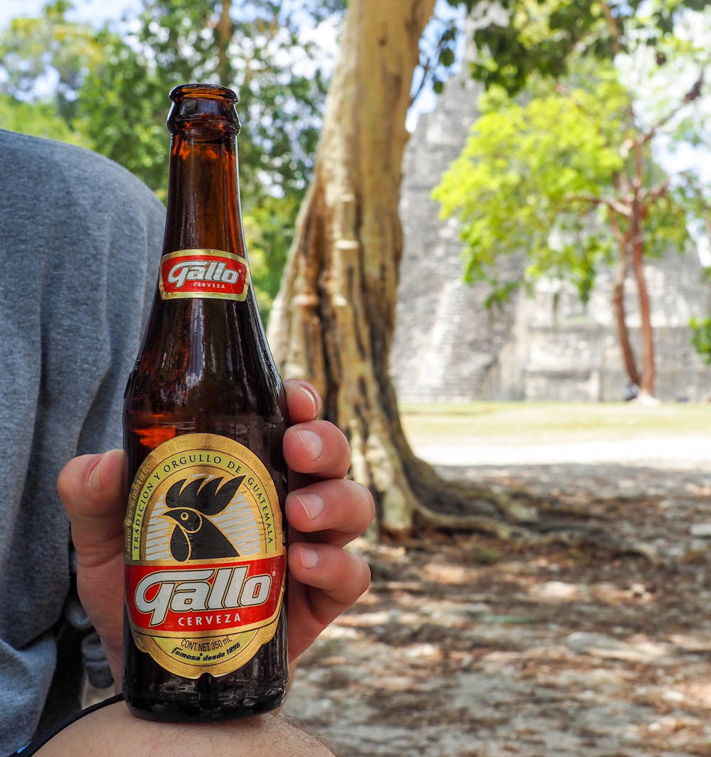 Man holding bottle of Gallo beer in front of ancient temple