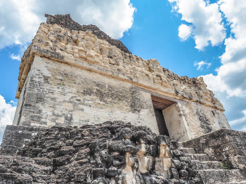top of ancient temple against blue sky on belize to tikal day trip
