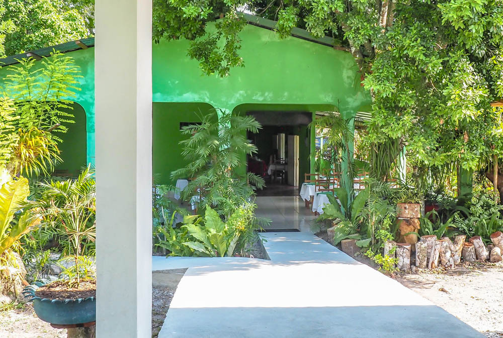 green building surrounded by trees on belize to tikal day trip
