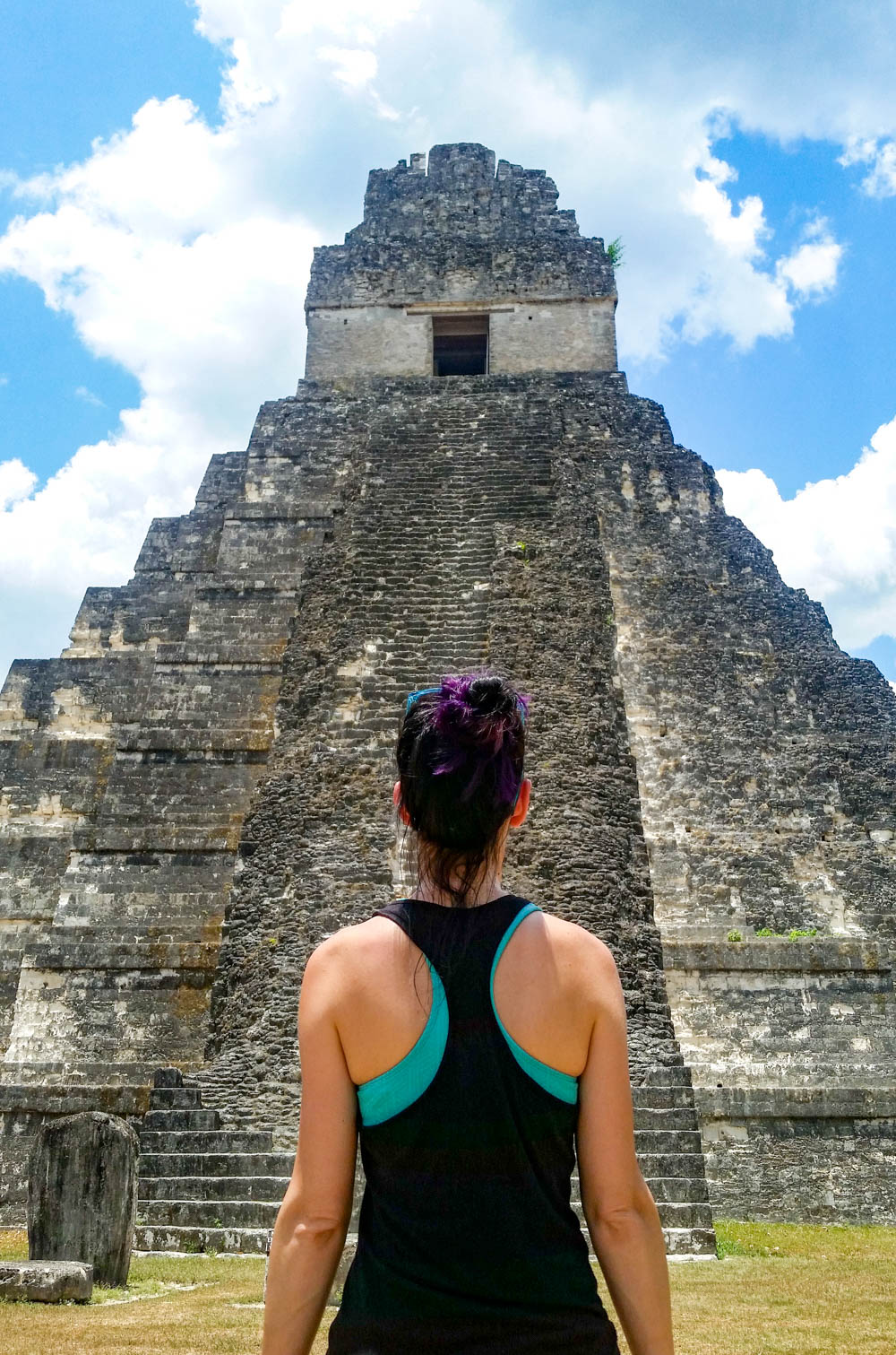 woman standing in front of and facing ancient temple on belize to tikal day trip