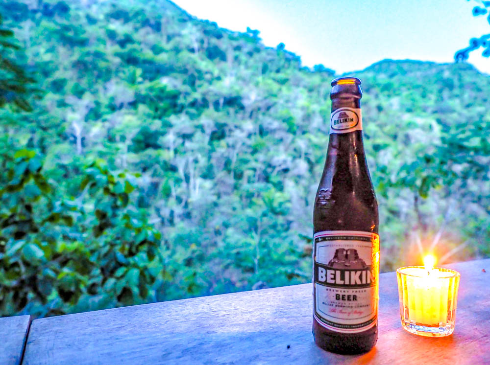 bottle of belikin beer next to a candle on a ledge overlooking the jungle at dusk