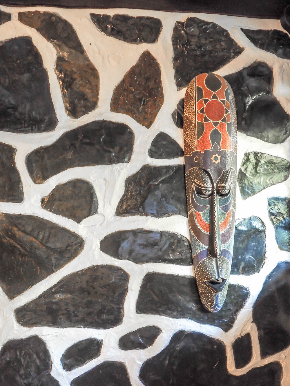 artistic mask hanging on a black and white stone wall