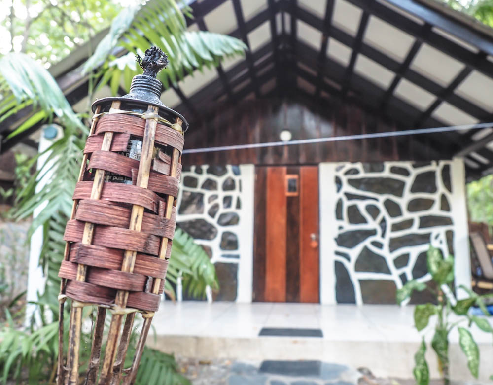 tiki torch in front of a brown and white jungle cabin at black rock lodge in belize