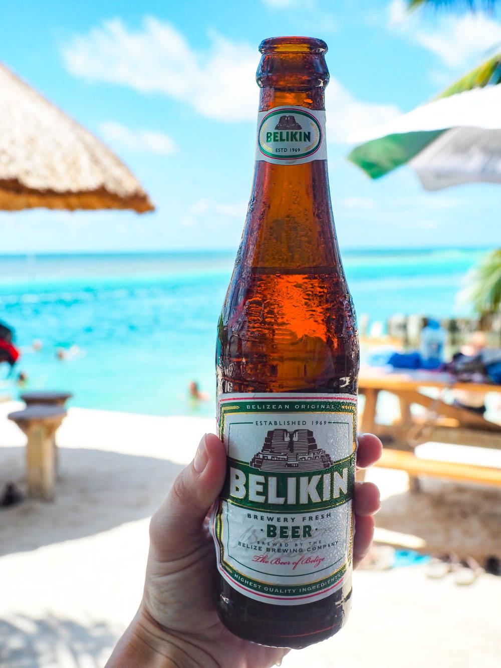 bottle of belikin beer in front of the ocean