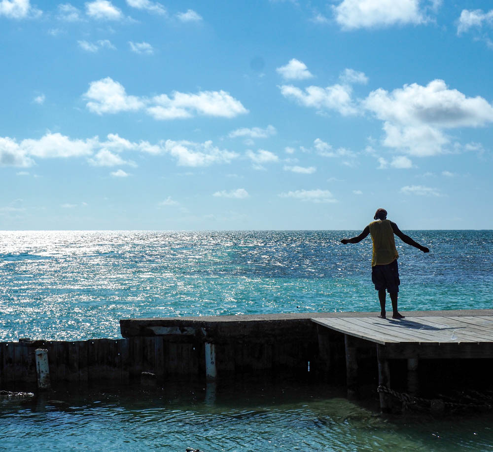man fishing on a dock over a turquoise ocean