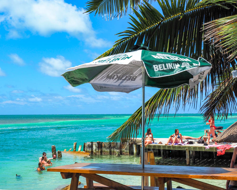 tiki bar next to turquoise ocean water and palm trees