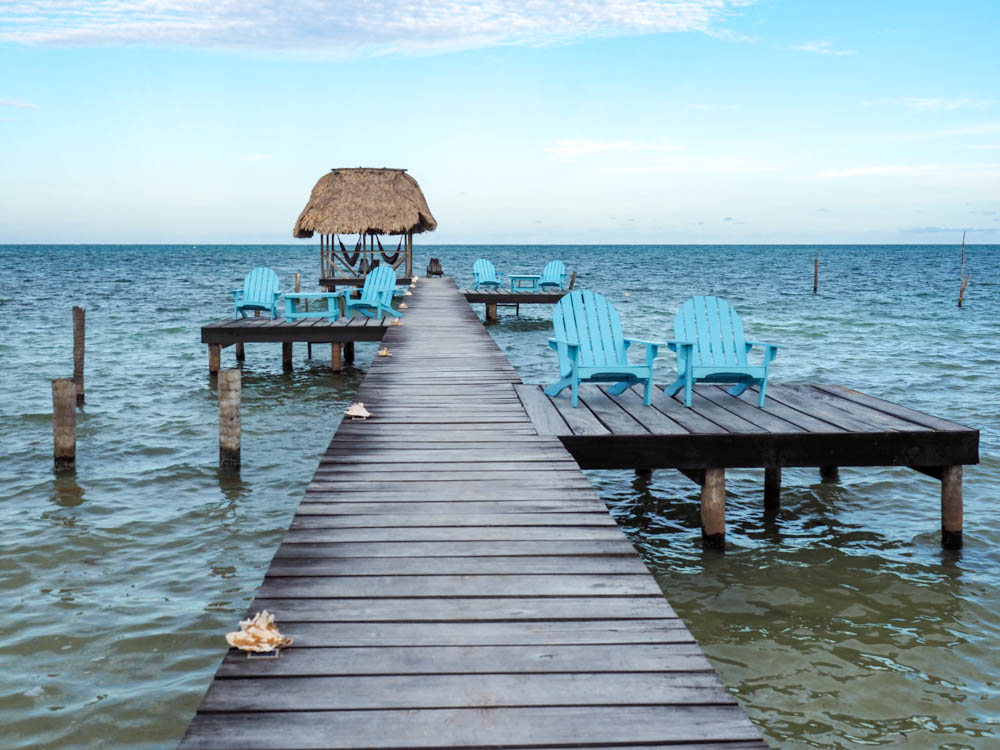 dock over the ocean with light blue chairs and conch shells