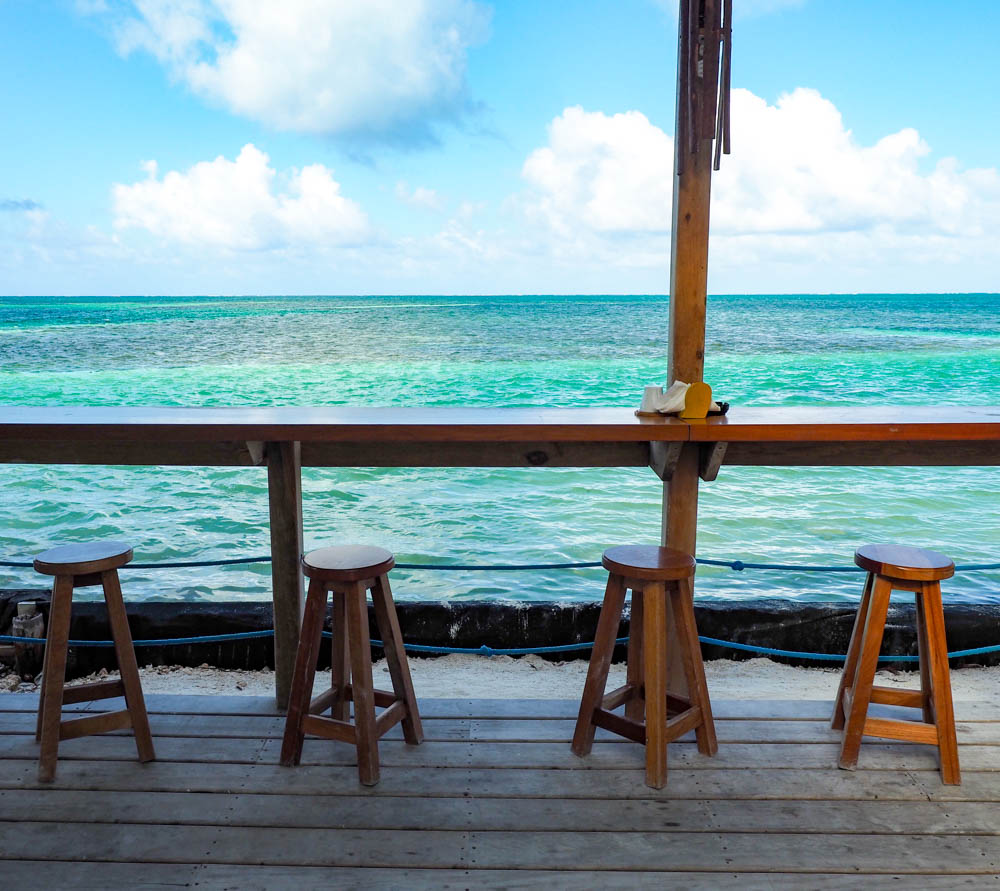 bar and stools in front of a turquoise ocean