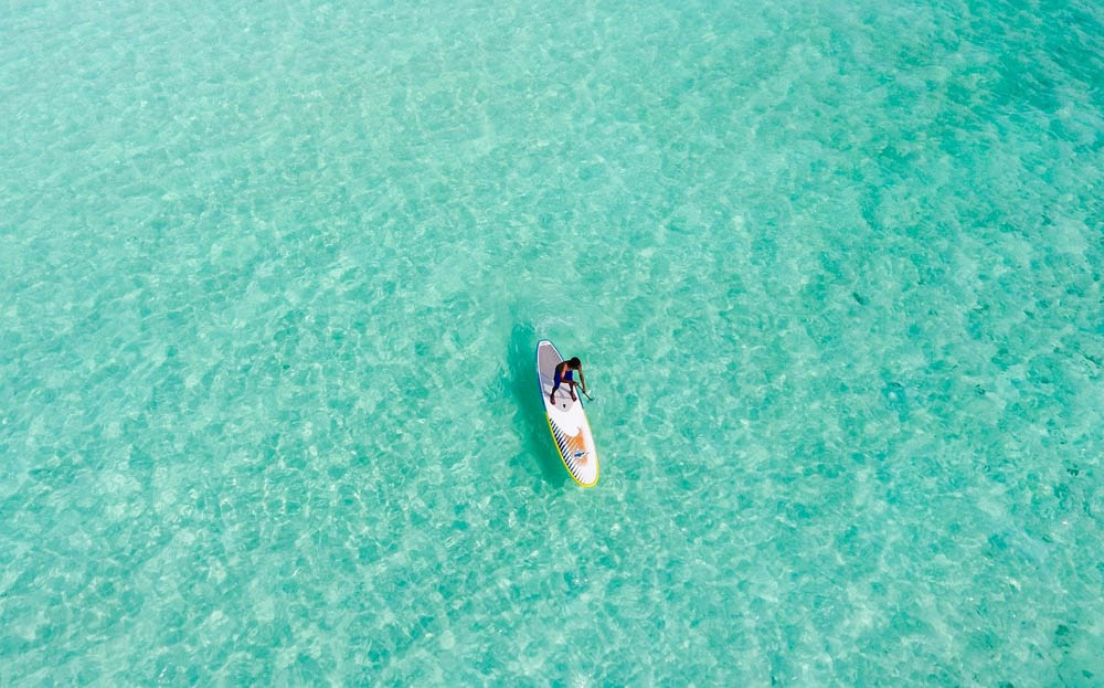 man stand-up paddle boarding in turquoise water seen from above