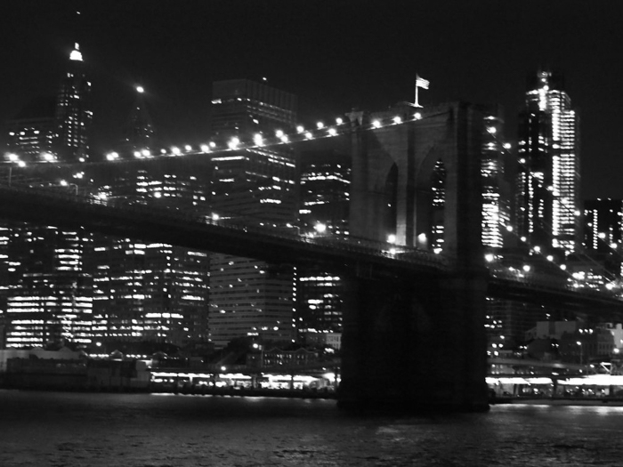 Brooklyn Bridge at night with the NYC skyline in the background, viewed from the water