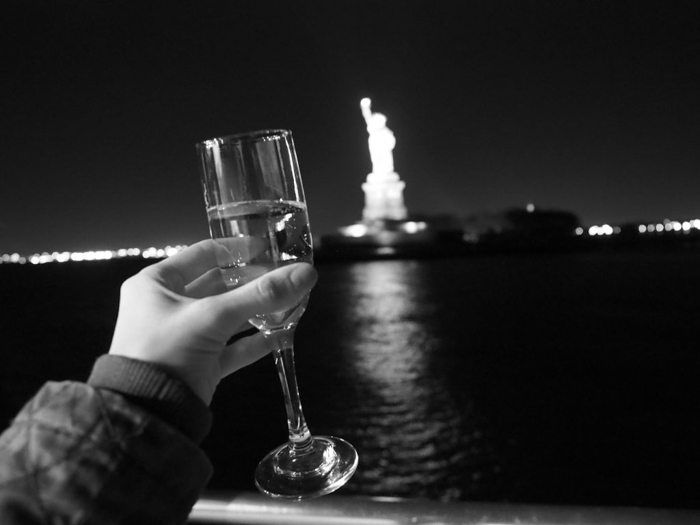 glass of champagne in front of the statue of liberty while on a thanksgiving dinner cruise nyc