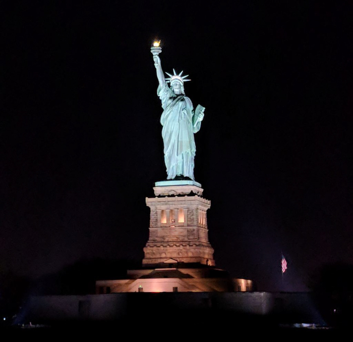 statue of liberty in the dark lit up at night