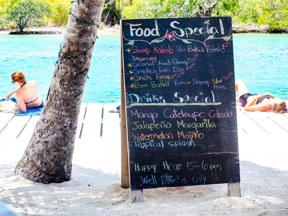food menu under a palm tree next to a turquoise ocean in belize