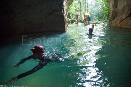 Man swimming into the ATM Cave / What to pack for the ATM Cave in Belize: What to wear, what shoes to wear, what to bring, and what to never, ever bring into the ATM Cave.