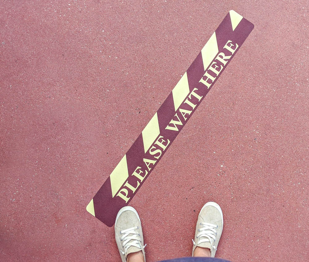 """feet next to a social distancing marker that says """"please wait here"""""""