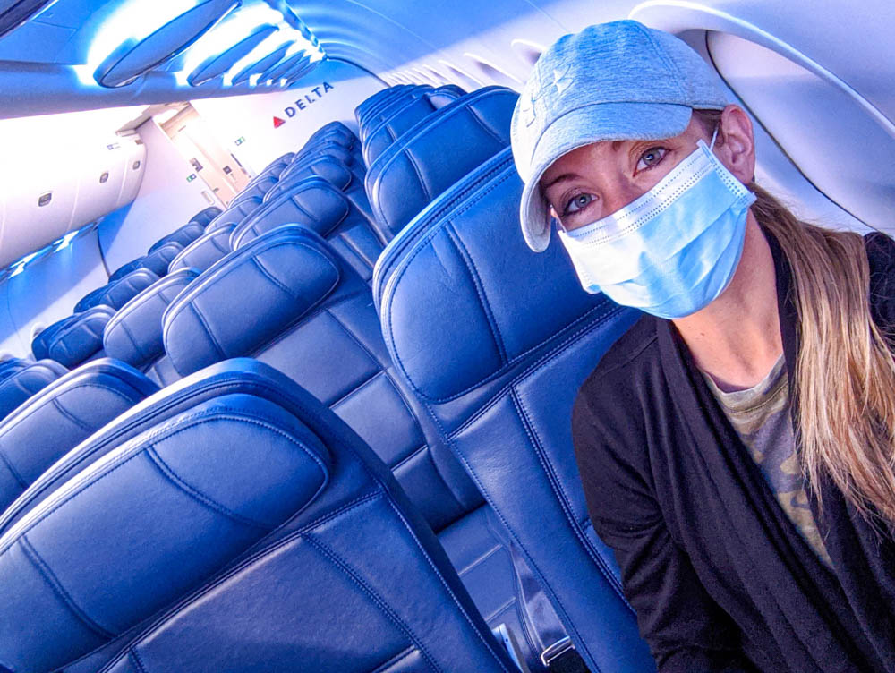Woman in baseball cap and mask on an empty airplane