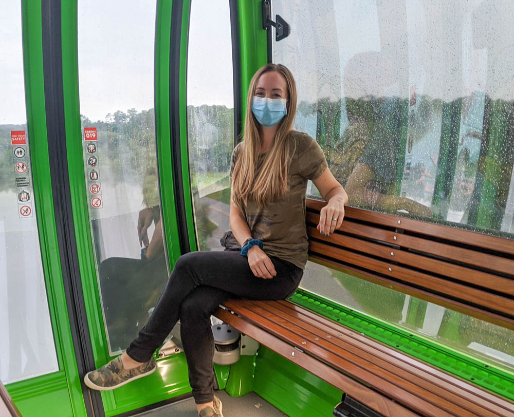 Blonde woman in a mask on the Disney skyliner gondola system
