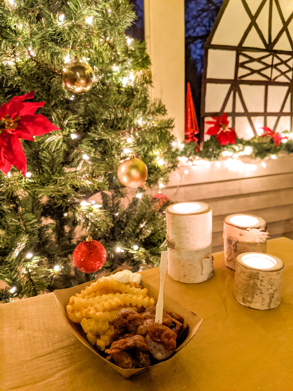 plate of currywurst and french fries in front of christmas decorations