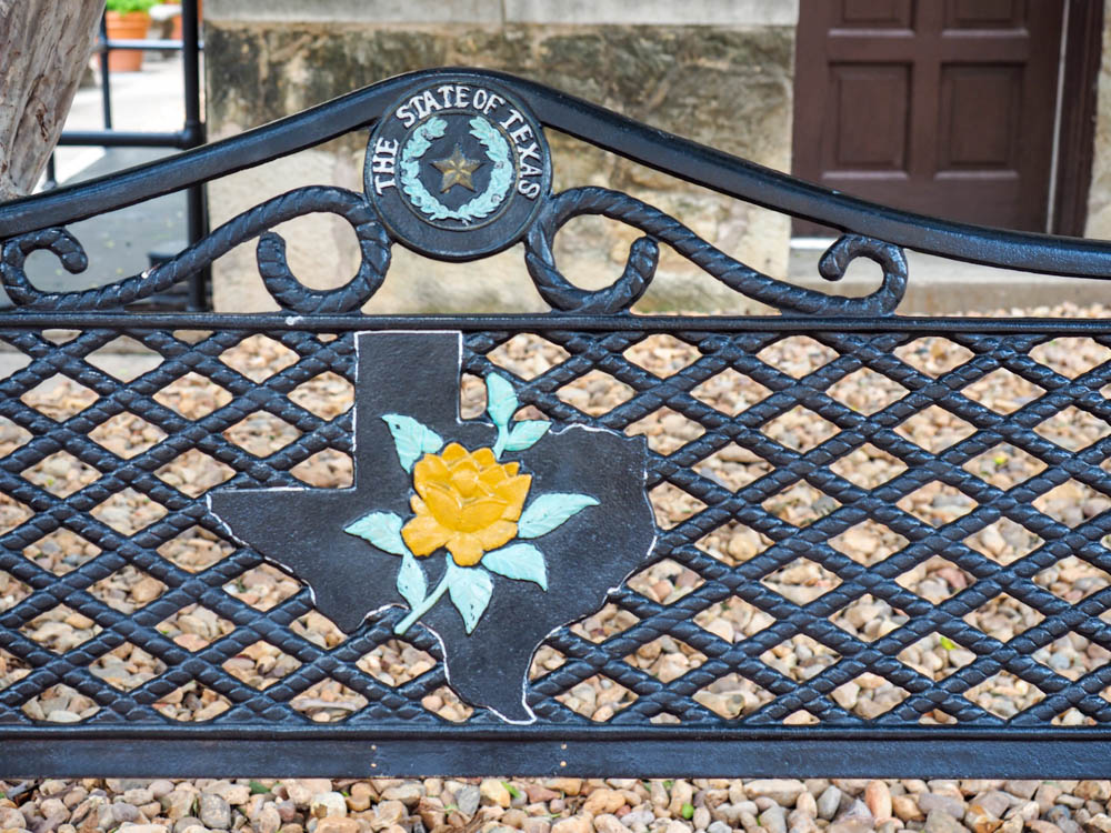 bench with yellow rose outside the historical sites in san antonio texas