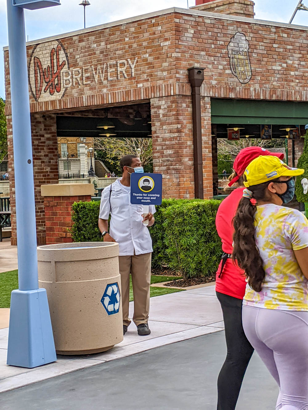 Employee holding mask sign at universal orlando during the pandemic