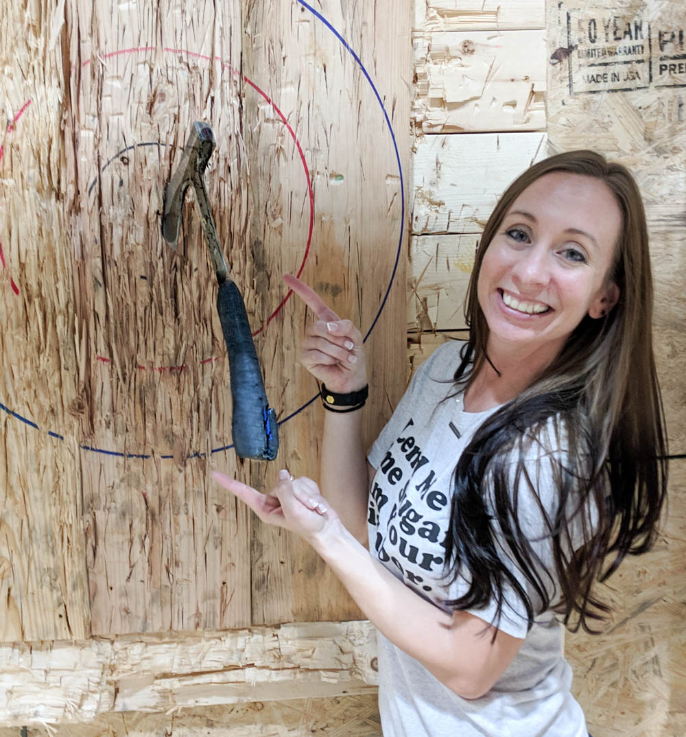 girl standing next to axe in a bullseye - things to do in orlando besides theme parks