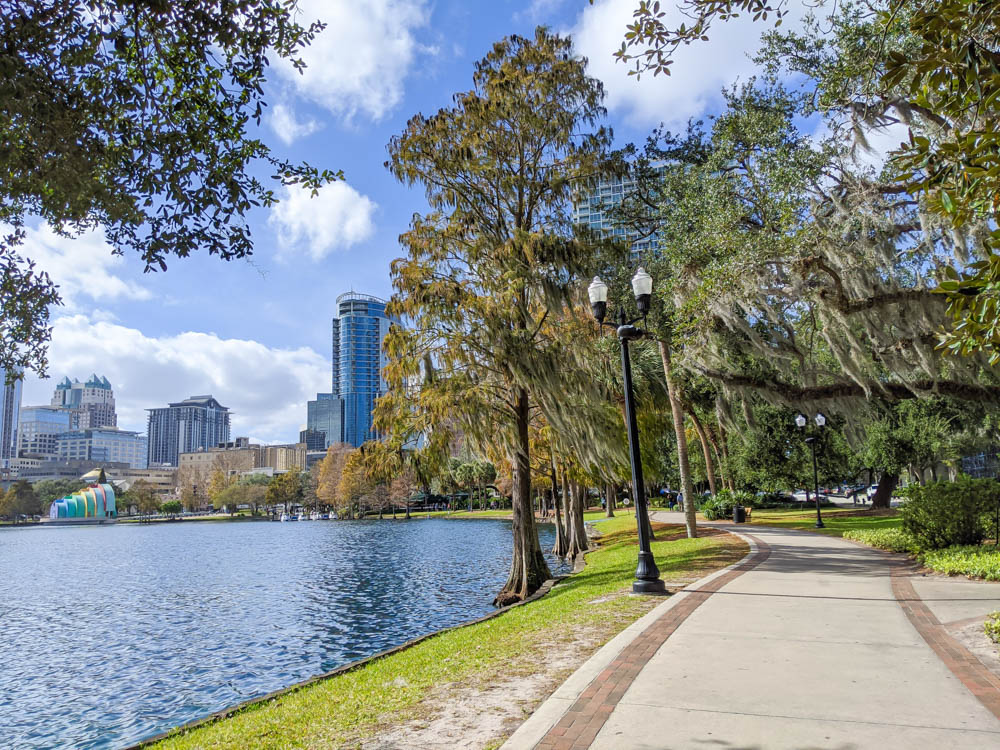 lake in front of urban skyline with walking path covered in spanish moss