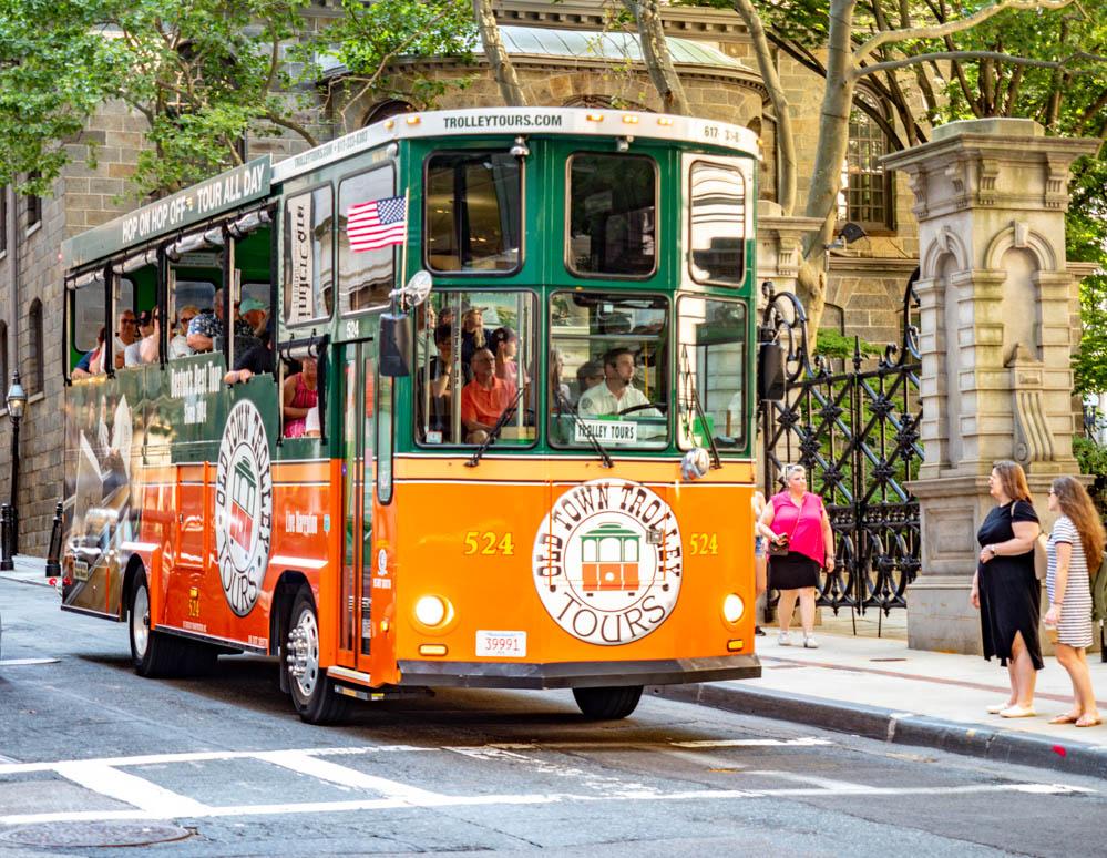 Green and orange Old Town Trolley Tour Bus driving through Boston